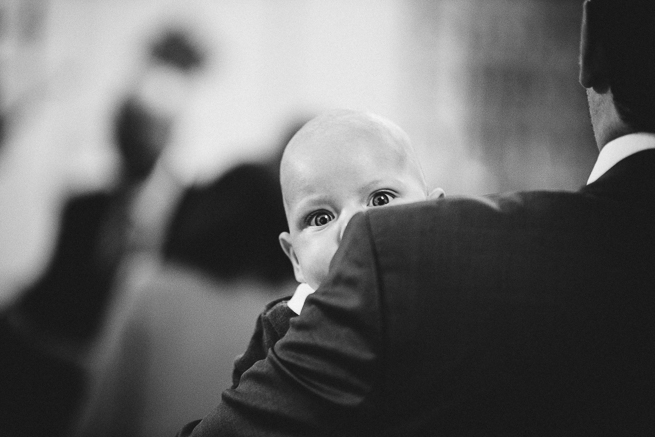 Baby looking over man's shoulder at a baptism